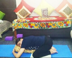 Child's pose on a bolster. Restaurant in Yoga posture for post corona illness recovery.